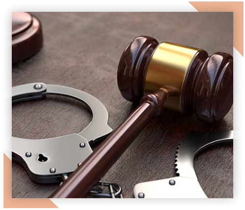 Placeholder image of a wooden gavel on a wooden table next to metal handcuffs.