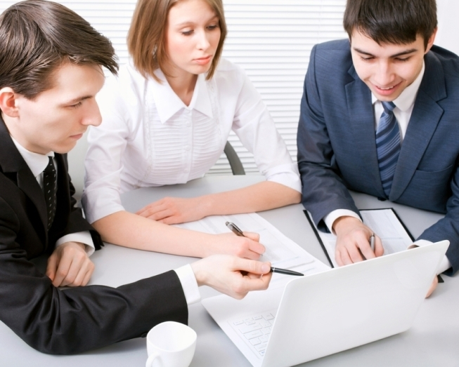 Placeholder image of 3 people sitting at a tale point at documents with their pens.